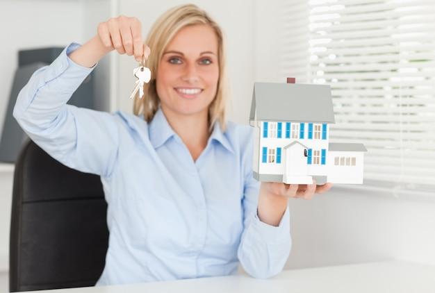 Wspaniały blondynka bizneswoman przedstawia modela dom i kluczy spojrzenia w kamerę