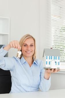 Wspaniały blondynki bizneswomanu seansu modela dom i kluczy spojrzenia w kamerę