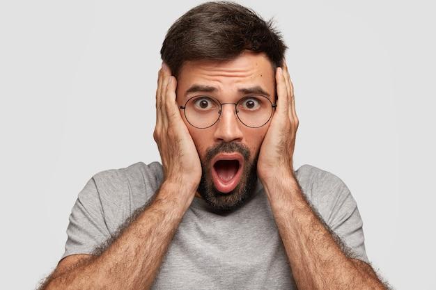 Wspaniały brodaty mężczyzna ze zszokowanym wyrazem twarzy, trzyma ręce na głowie, szeroko otwiera usta, ubrany w zwykłą szarą koszulkę, okrągłe okulary, słyszy przerażające wieści, odizolowany na białej ścianie