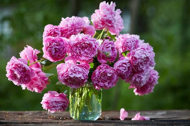Wspaniały bukiet różowe piwonie w banku na drewnianym stole na naturze