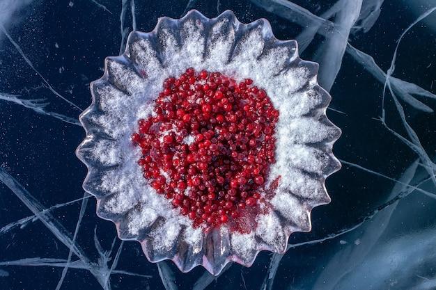 Wspaniały ciemny lód z pęknięciami i danie lodowe z żurawiną. czerwone jagody na pokrojonych w lodzie potrawach. rosyjski, syberyjski zwyczaj spotykania się z gośćmi nad bajkałem. poziomy.