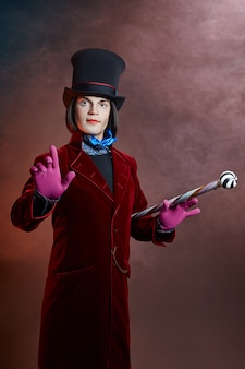 Wspaniały cyrkowy mężczyzna w kapeluszu i czerwonym garniturze pozuje w dymie