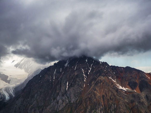 Wspaniały dramatyczny krajobraz z dużymi ośnieżonymi szczytami górskimi nad niskimi chmurami. atmosferyczne duże szczyty górskie śniegu w zachmurzonym niebie.