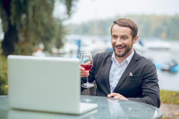 Wspaniały dzień. młody dorosły wesoły człowiek w garniturze z kieliszek do wina przed laptopem na zewnątrz