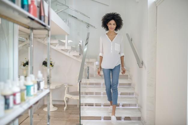 Wspaniały dzień. uśmiechnięta młoda dziewczyna chodzenie po schodach w centrum urody w ubranie