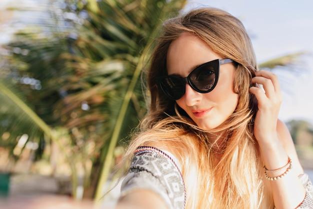 Wspaniały kaukaski kobieta robi selfie na plaży z palmami. plenerowe zdjęcie uroczej dziewczyny w czarnych okularach przeciwsłonecznych spędzających wakacje w egzotycznym kraju.