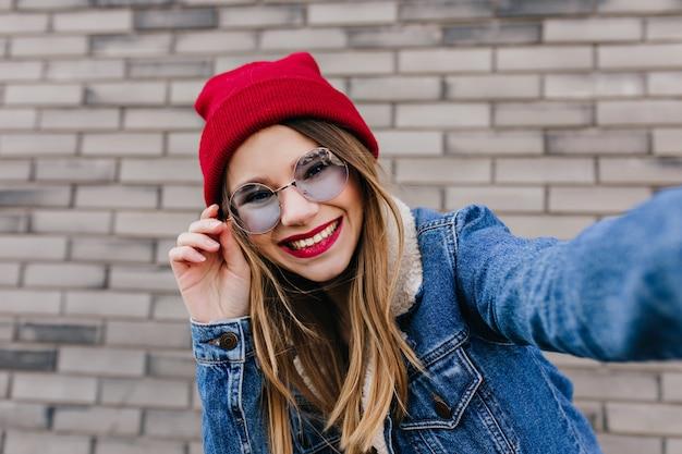 Wspaniały kaukaski modelka figlarnie dotykając jej okulary przeciwsłoneczne. odkryty strzał śmiejąc się modnej kobiety z jasnymi włosami pozowanie w pobliżu ściany z cegły.