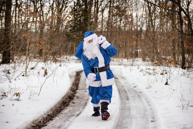Wspaniały krajobraz pokryty śniegiem święty mikołaj w niebieskim garniturze na bajkowym zimowym lesie z drzewami