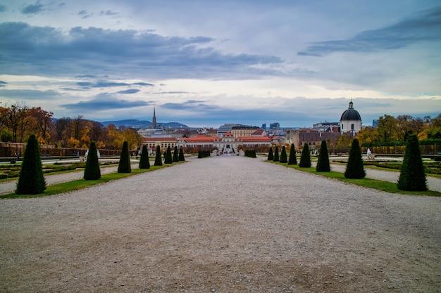Wspaniały krajobraz z szeroką główną aleją spacerową przed unteres belvedere z regularnym sadzeniem drzew i roślin w wiedniu, austria na tle zachmurzonego nieba.