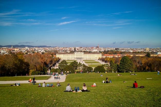 Wspaniały krajobraz z widokiem na pałac schonbrunn w wiedniu, austria i zielone szerokie pole trawy z siedzącymi i relaksującymi ludźmi na ziemi na tle błękitnego nieba.
