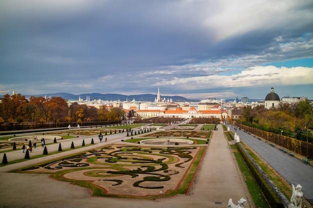 Wspaniały krajobraz z widokiem na unteres belvedere i ogród parter regularnego sadzenia drzew i kwiatów w wiedniu, austria na tle szarego pochmurnego nieba jesienią.
