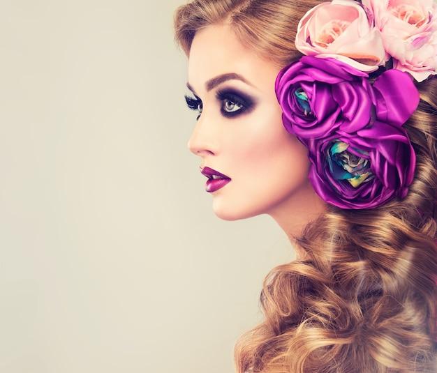 Wspaniały makijaż w stylu smokey eyes na twarzy młodej, pięknej kobiety
