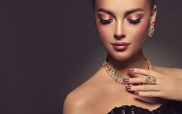 Wspaniały makijaż z długimi czarnymi rzęsami i ciemnoróżową szminką na twarzy ładnej kobiety french manicure na paznokciach zbliżenie portret pięknej modelki ubranej w pozłacaną biżuterię