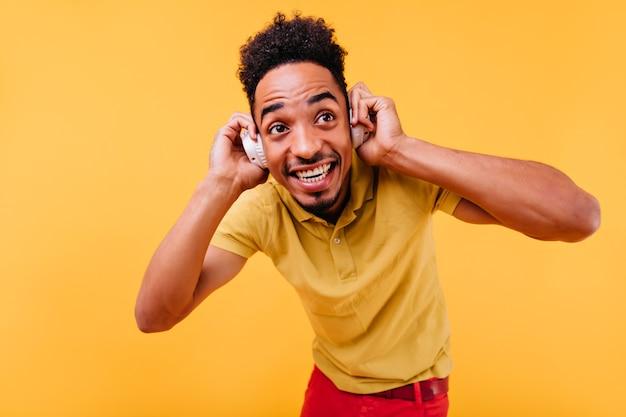 Wspaniały mężczyzna o wielkich ciemnych oczach słuchający muzyki. kryty zdjęcie radosnego afrykańskiego modelu męskiego w białych słuchawkach.