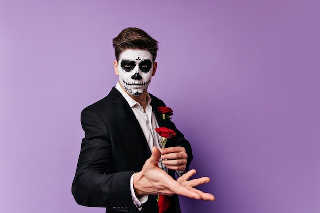 Wspaniały młody człowiek ze sztuką twarzy w postaci czaszki trzymając czerwoną różę w dłoniach, pozuje do portretu na na białym tle.