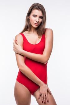 Wspaniały model dziewczyna w czerwonym apartamencie pływackim trzyma ręce na nogach na białym tle