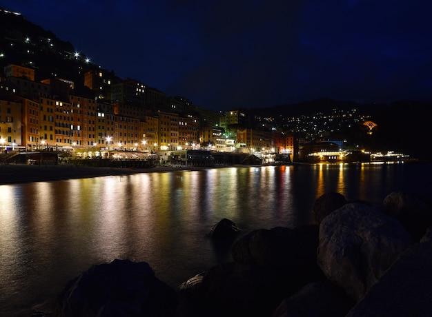 Wspaniały nocny widok miasta camogli z kolorami świateł i odbiciami na morzu