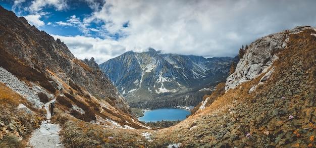 Wspaniały panoramiczny widok na krystalicznie czyste górskie jezioro strbske pleso w malowniczej dolinie. potężne, pokryte śniegiem tatry w parku narodowym na słowacji. spokój dzikiej dziewiczej przyrody.