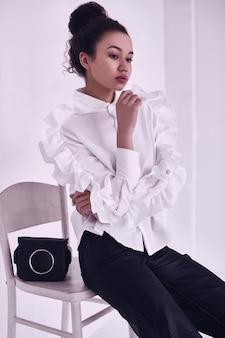 Wspaniały portret eleganckiej czarnej kobiety z kręconymi włosami w modnym garniturze na białym tle