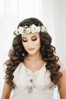 Wspaniały portret pięknej narzeczonej z makijażem ślubnym i długimi kręconymi włosami nosi wieniec cristal i suknię ślubną z koronki.