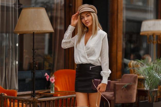 Wspaniały seksowny blond model pozuje w pobliżu kawiarni