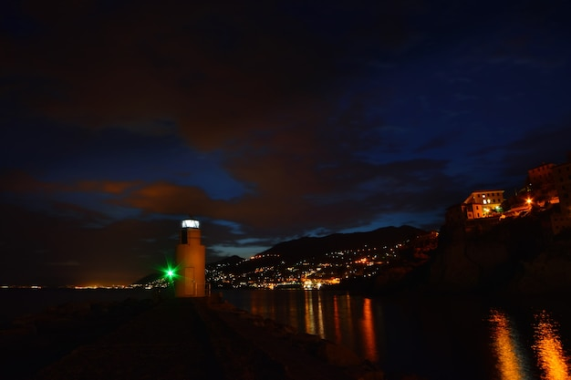 Wspaniały widok na latarnię morską w camogli światła i kolory odbijają się w morzu, tworząc a