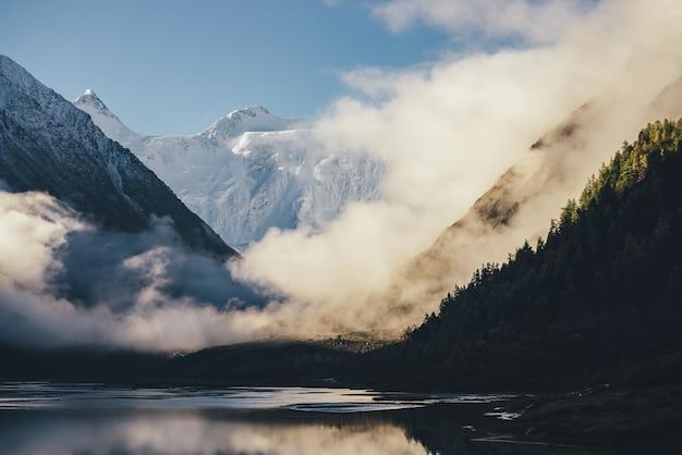 Wspaniały widok na ośnieżone góry nad gęstymi chmurami w złotym słońcu. malowniczy krajobraz z alpejskim jeziorem, sylwetką lasu iglastego i wysoką biało-śnieżną górą wśród gęstych niskich chmur