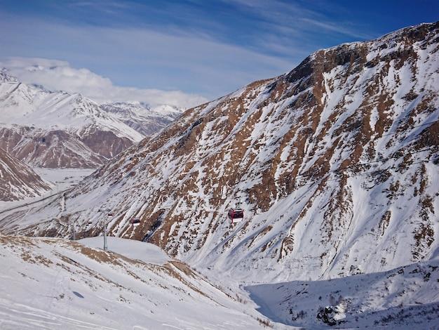Wspaniały widok na pasma górskie w śniegu i kolejkę linową w kurorcie śnieżnym