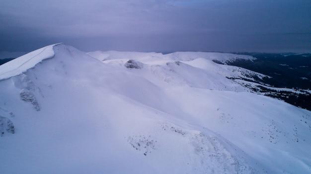 Wspaniały widok na pokryte śniegiem klify i drzewa w pochmurny zimowy dzień w ośrodku narciarskim