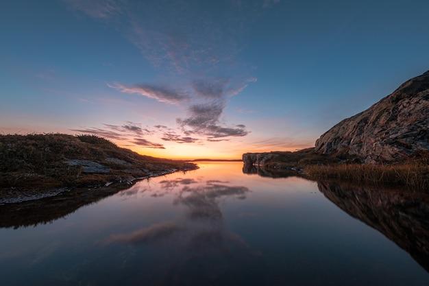 Wspaniały widok na spokojne jezioro otoczone skałami, z niebem odbijającym się w wodzie podczas zachodu słońca