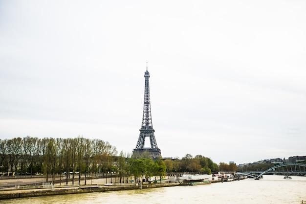 Wspaniały widok na wieżę eiffla w paryżu. la tour eiffel z niebem i łąkami.