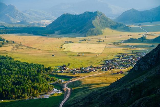 Wspaniały widok na wioskę wśród wielkich leśnych wzgórz i gór w wieczornym świetle. wiele małych domów w słońcu. piękna zielona alpejska wieś. niesamowita górska wioska. kraj kraju o zachodzie słońca.