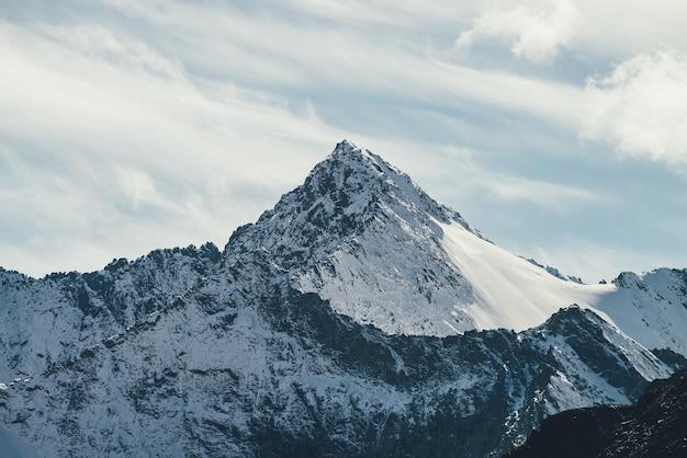 Wspaniały widok na wysoką zaśnieżoną ścianę górską z daszkiem pod chmurami cirrus na niebie. alpejski krajobraz z dużymi górami pokrytymi śniegiem z ostrym szczytem w słońcu. biały śnieżno-szpiczasty szczyt w słońcu.