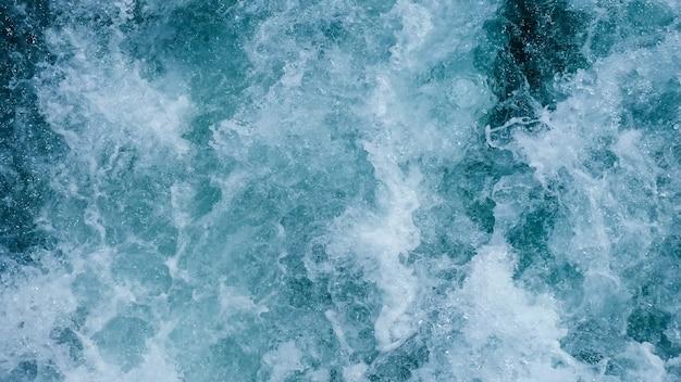 Wspaniały widok statku płynącego po spokojnym morzu, poruszającego się wzdłuż turystycznego miasta ze słynnymi zabytkami pod błękitnym niebem