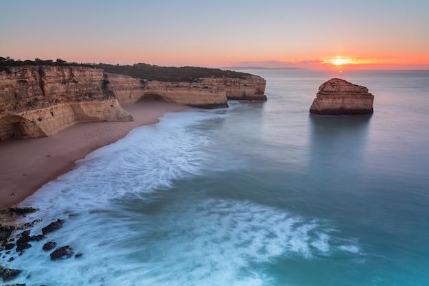 Wspaniały wschód słońca na plaży. w albufeirze. seagull odpoczywa na brzeg.