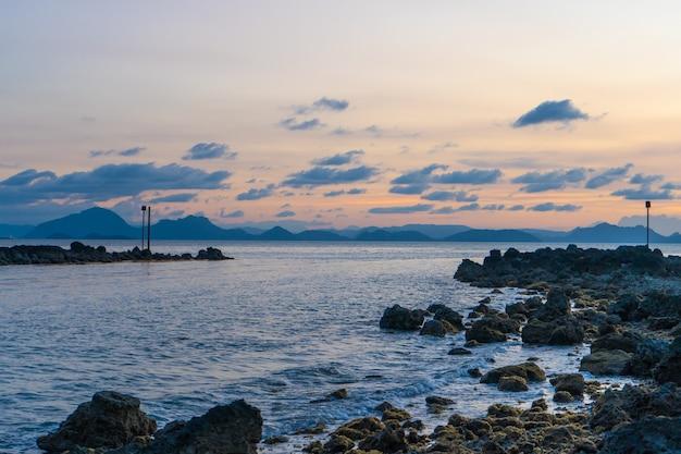 Wspaniały zachód słońca nad brzegiem morza, kolory zachodzącego słońca i sylwetka wyspy na wodzie. niesamowity tropikalny zachód słońca.