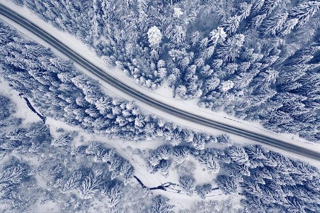 Wspaniały zimowy krajobraz górski. droga w śnieżnym lesie zimą. widok z drona.
