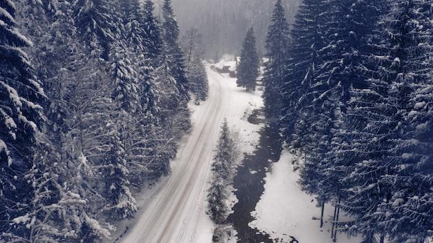 Wspaniały zimowy krajobraz górski, zaśnieżona górska droga z zakrętami i lasem na horyzoncie.
