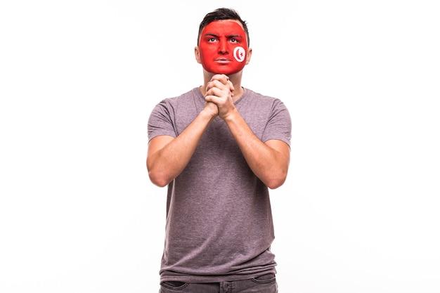 Wsparcie fanów reprezentacji tunezji modli się z pomalowaną twarzą na białym tle