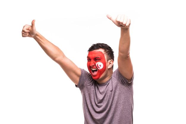 Wsparcie fanów reprezentacji tunezji z pomalowaną twarzą, krzykiem i krzykiem na białym tle