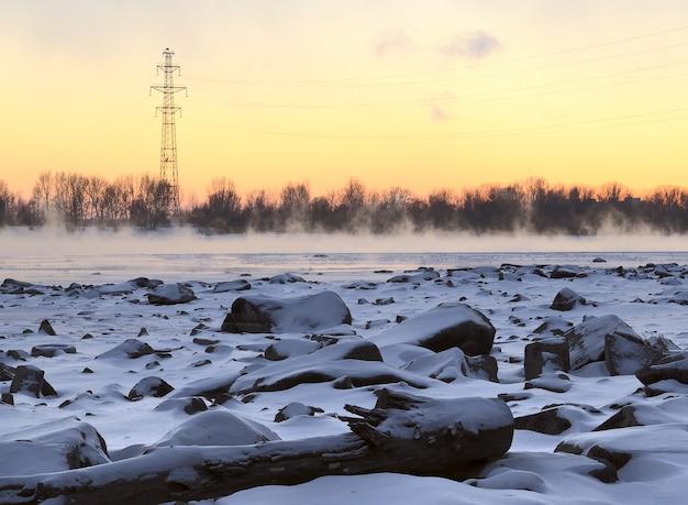 Wsparcie linii energetycznej na zimowym brzegu ob skalisty brzeg rzeki ob pokryty jest śniegiem
