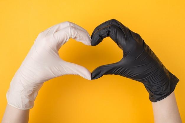 Wsparcie podczas kwarantanny koronawirusa. zdjęcie z góry nad głową przedstawiające kobiece dłonie w czarno-białych rękawiczkach, tworzące serce na białym tle na żółtym tle