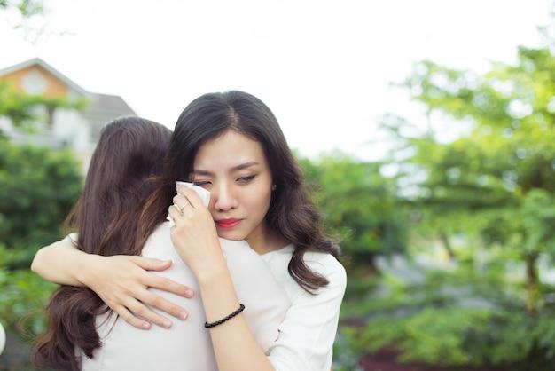 Wsparcie pomocy przyjaźni. przygnębiona azjatka obejmująca swojego przyjaciela.