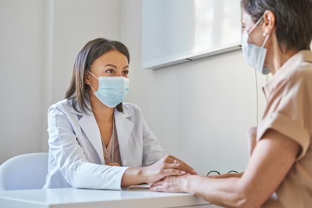 Wspierająca afroamerykańska lekarka w masce ochronnej na twarz trzymająca rękę pacjenta, wyrażająca troskę i pocieszająca kobieta w średnim wieku odwiedzająca klinikę podczas pandemii covid-19 i wybuchu grypy