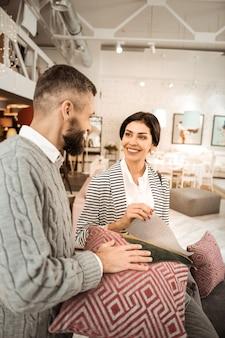 Wspierający mąż. atrakcyjna ciemnowłosa kobieta rozmawiająca z mężem o projektach podczas pobytu w salonie z meblami