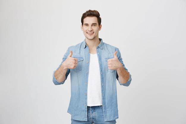 Wspierający przystojny mężczyzna kciuki w górę z aprobatą