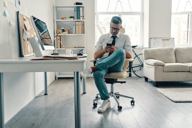 Wspieranie klientów. rozważny młody człowiek w koszuli i krawacie za pomocą smartfona siedząc w biurze