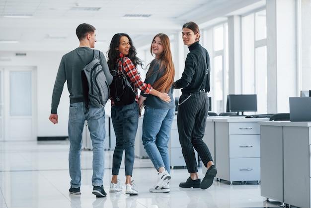 Wspieranie się nawzajem. grupa młodych ludzi chodzących po biurze w czasie przerwy