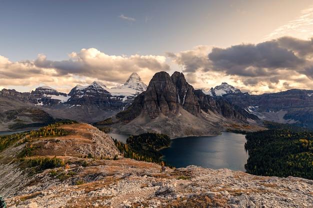 Wspina się assiniboine z jeziorem na szczyt nublet w jesień lesie na zmierzchu przy parka prowincjonalnego