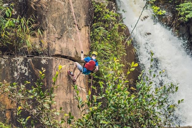 Wspinacz na powierzchni pięknego kaskadowego wodospadu datanla w górskim miasteczku dalat, wietnam
